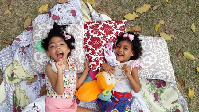 Two girls laughing as they lie on pillows in the park