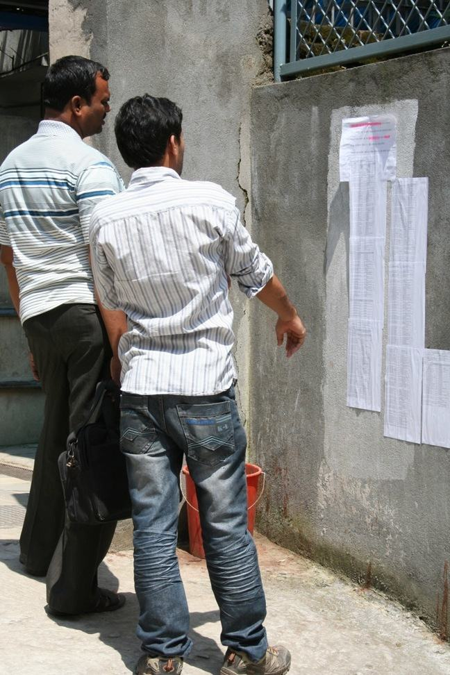 Picture showing Nepalese men looking at job advertisements.