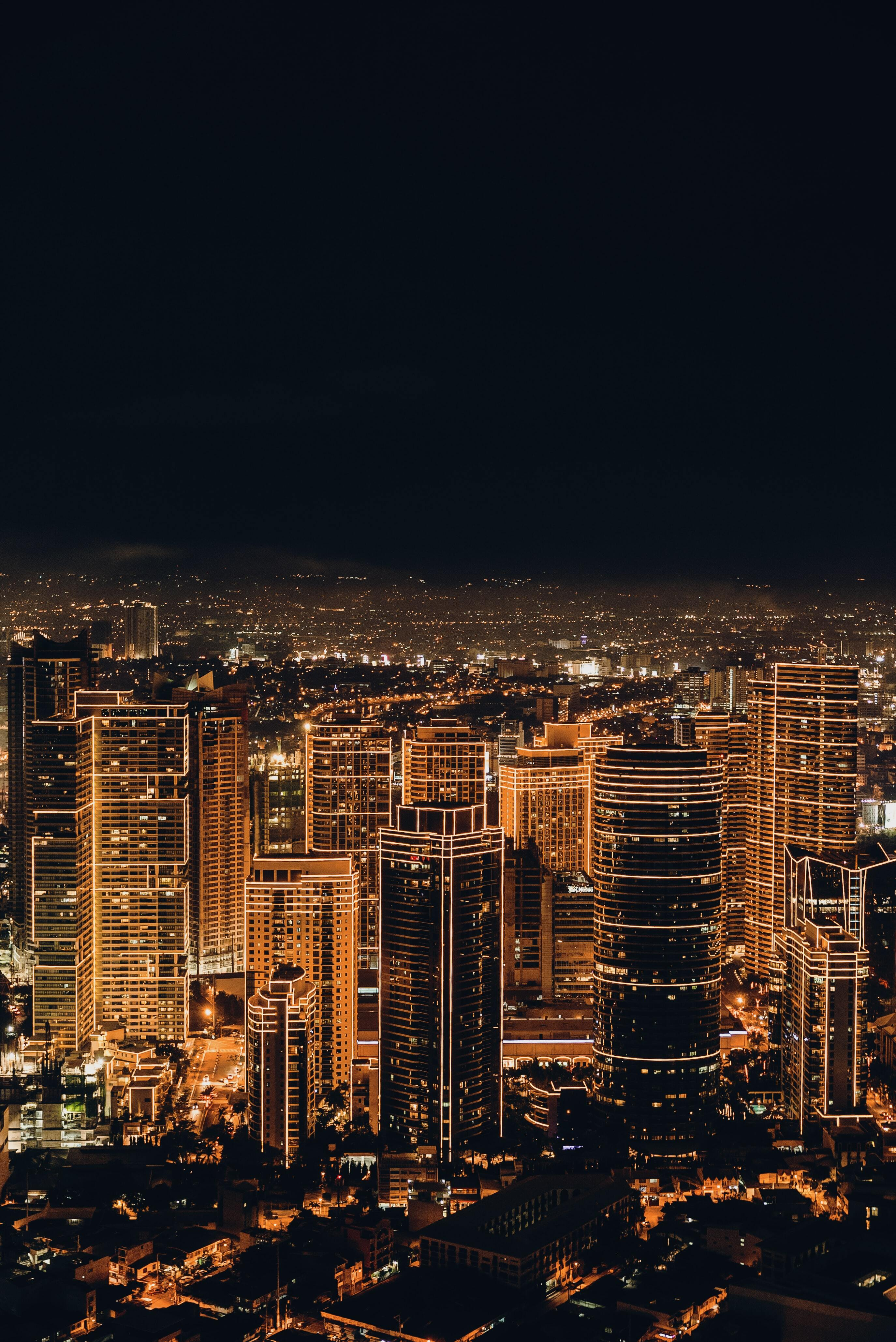 Photograph of a city skyline at night illuminated by skyscrapers and road network
