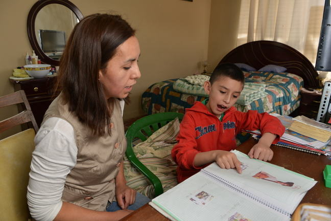 A boy with a hearing impairment is pointing at a book with images in. He is being supported by a woman. They are in a bedroom