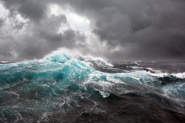 Colour enhanced photograph of a turbulent sea with waves and white crests, against grey clouds with a hint of blue sky through a break in the clouds