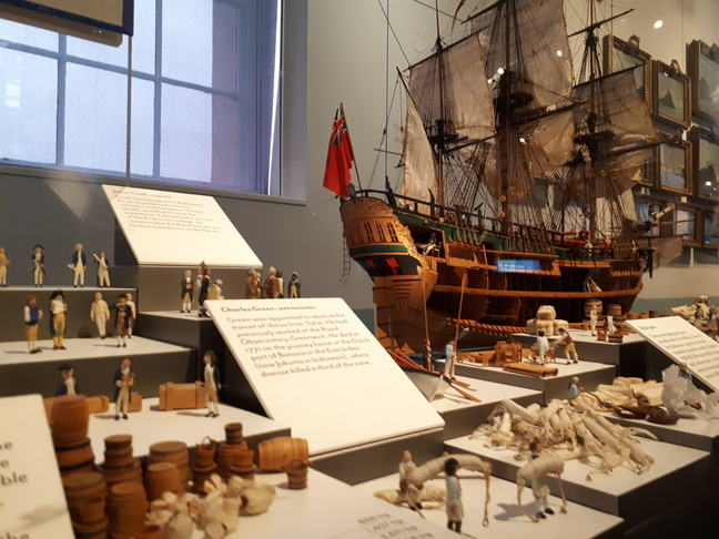 Endeavour ship model showing ship model with crewmen figures and items from the voyage in the foreground such as barrells, rope, sailcloth