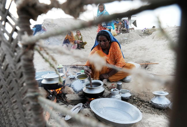 Photograph of a Pakistani woman displaced by floods preparing food for her family on higher ground in Khairpur Nathan Shah in southern Sindh province on September 6, 2010.