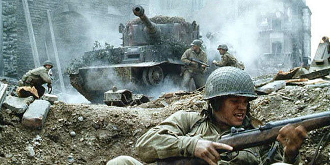 Still from the film Saving Private Ryan. A war torn street. A tank and a number of uniformed soldiers with rifles.