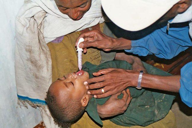Health worker squeezes tube of POS into child's mouth