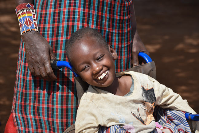A girl with cerebral palsy sitting in a wheelchair and smiling.