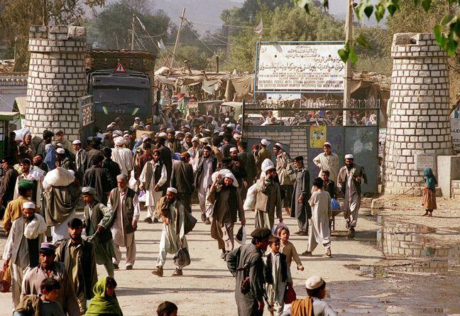 Photograph of Afghan refugees entering Pakistan across the Torkham border carrying their meagre belongings 03 November 2000