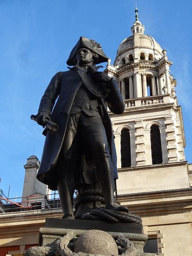 Statue of James Cook against blue sky background and white domed building in the Mall, London