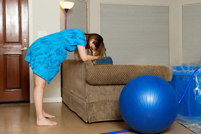 Pregnant woman leaning against sofa