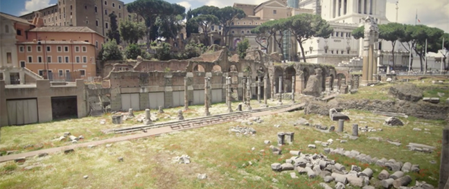 A photo of the Forum of Caesar. Large pieces of stone on the ground surrounded by grass