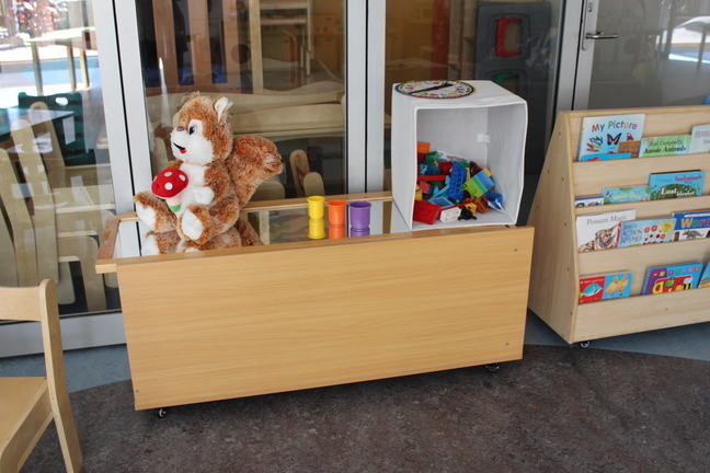 photograph of a bench of toys in an early childcare centre that has no chairs