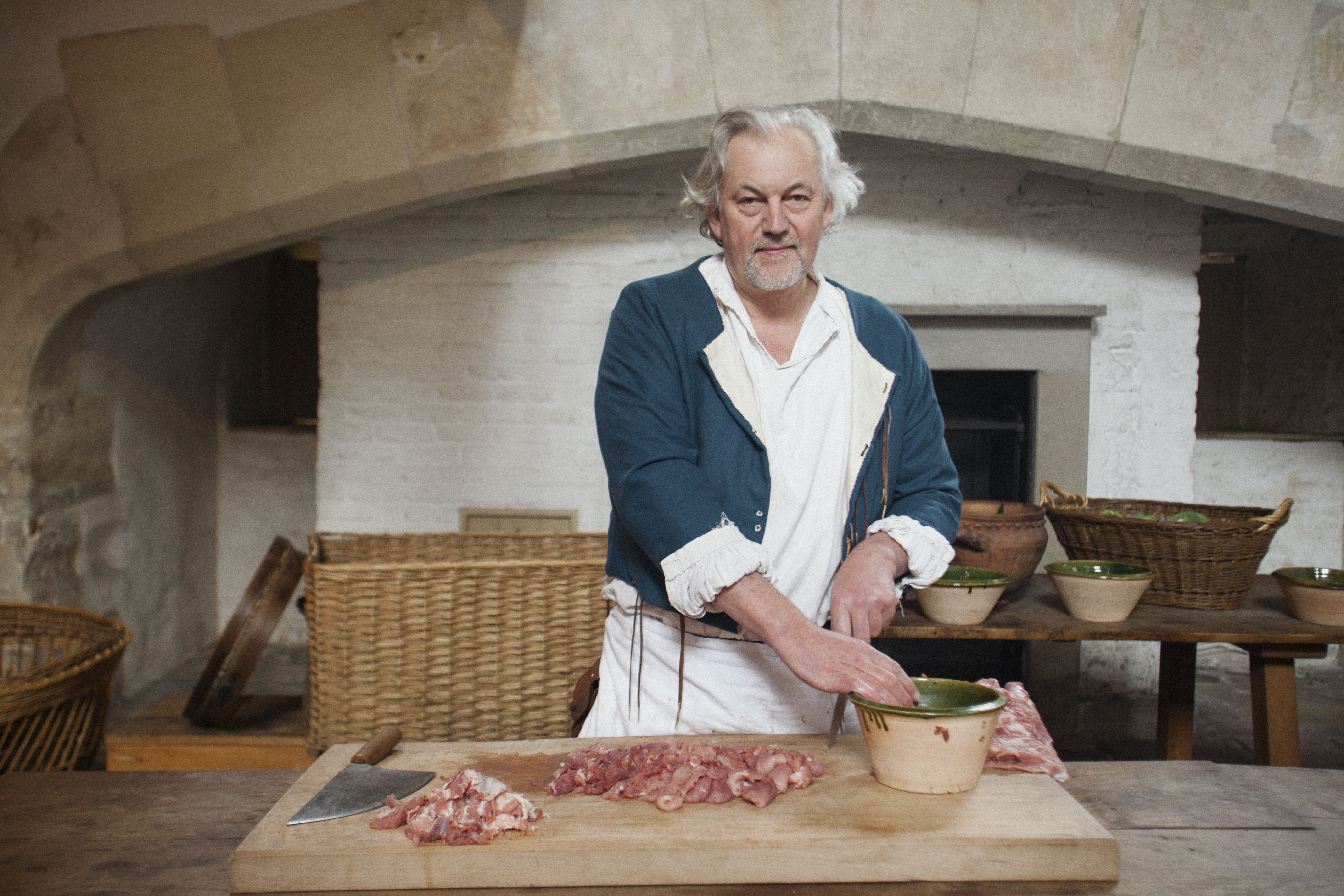 A photograph of a reenactment in a kitchen, with a cook dicing meat.