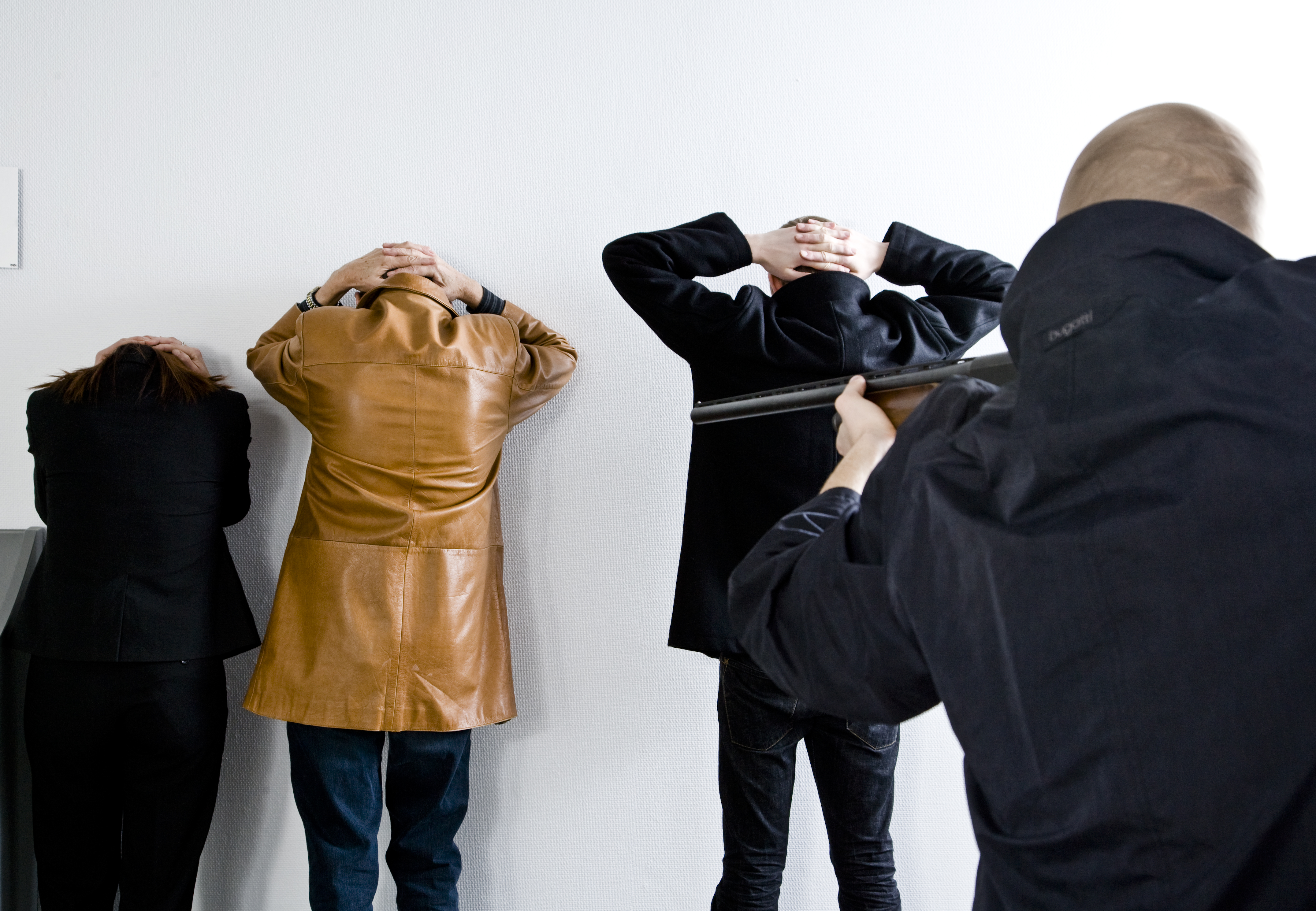Three people standing againt the wall with their hands behind their head, while another is pointing at them with a gun