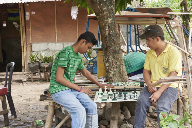 A teenager is playing chess with his father. Both are sitting on the table as they play