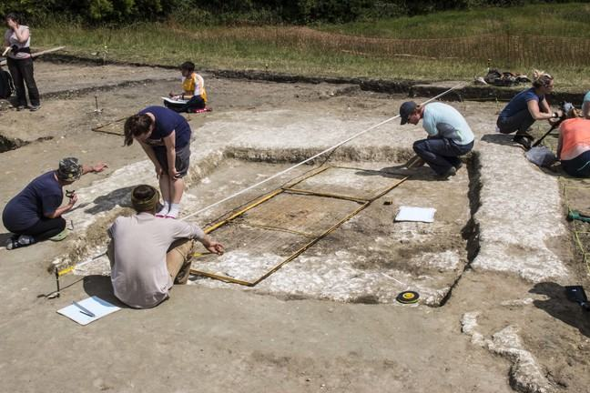 A photo of students excavating a chalk floor