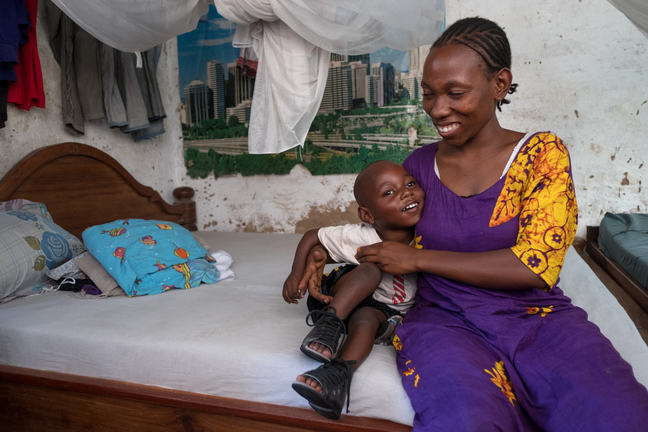 A boy is curling up to his mother and smiling as they sit on a bed.