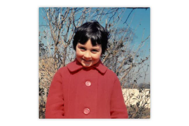 A photo of a girl smiling in a red coat