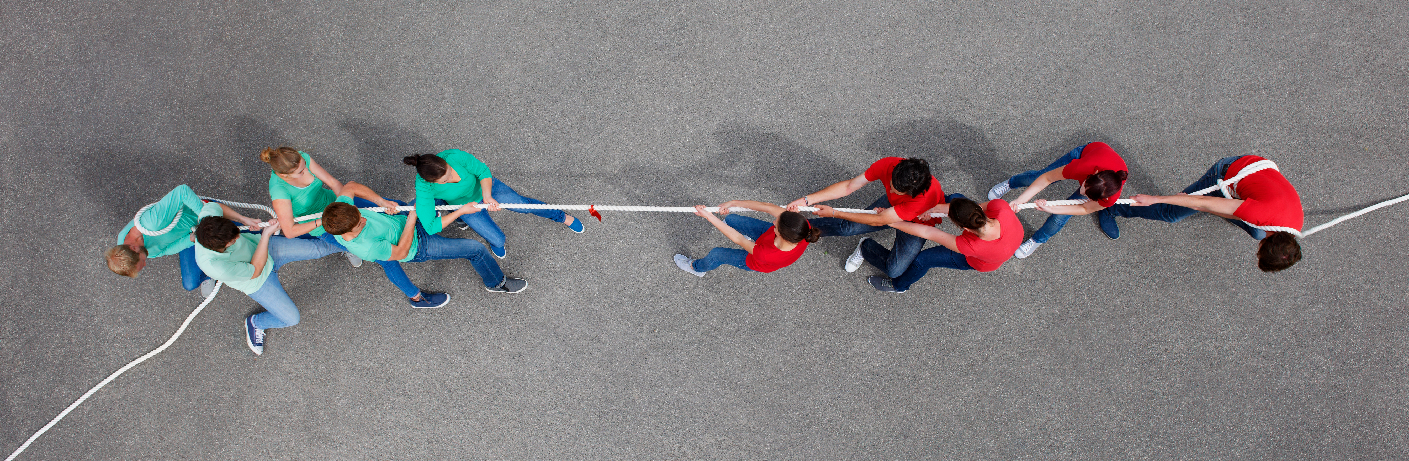 two opposing teams, one in blue t-shirts and the other in red t-shirts playing tug of war