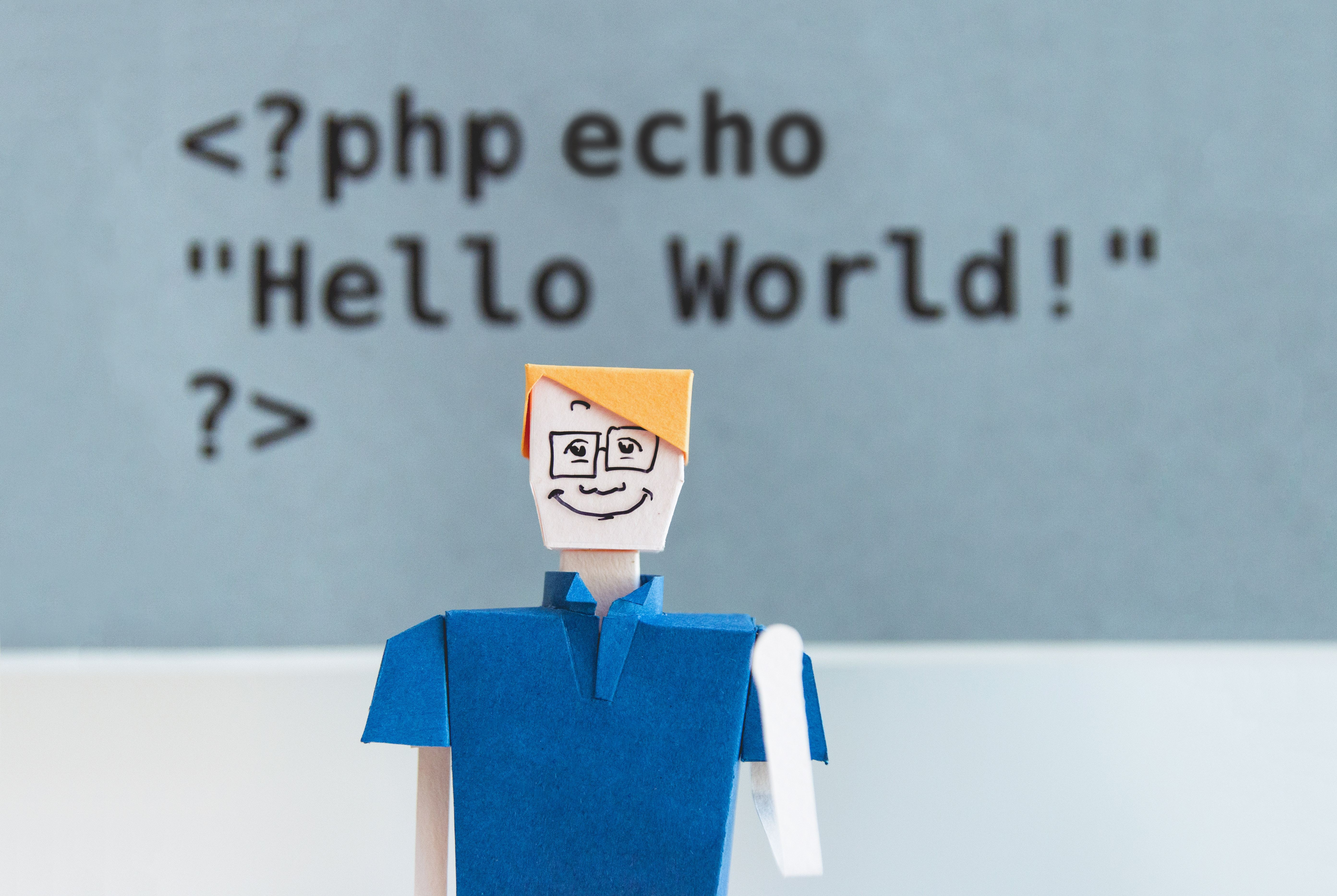 Paper cut our image of a man in a blue shirt smiling with caption 'Hello World' behind him