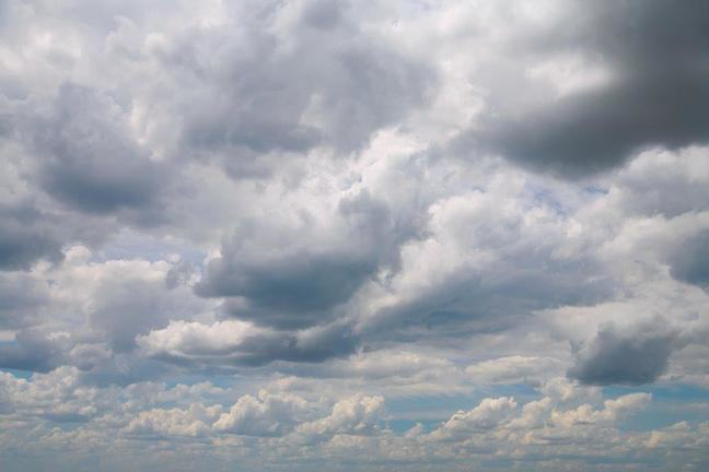 Photograph of a cloudy sky with just a few glimpses of blue visible in the cloud breaks