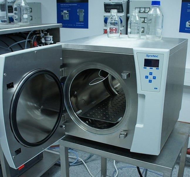 Picture of an Autoclave with the circular door open on a table. Inside the machine is a shelf