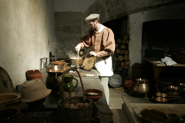 A photograph of a reenactment with a Georgian cook, stirring a pot which is on a stove