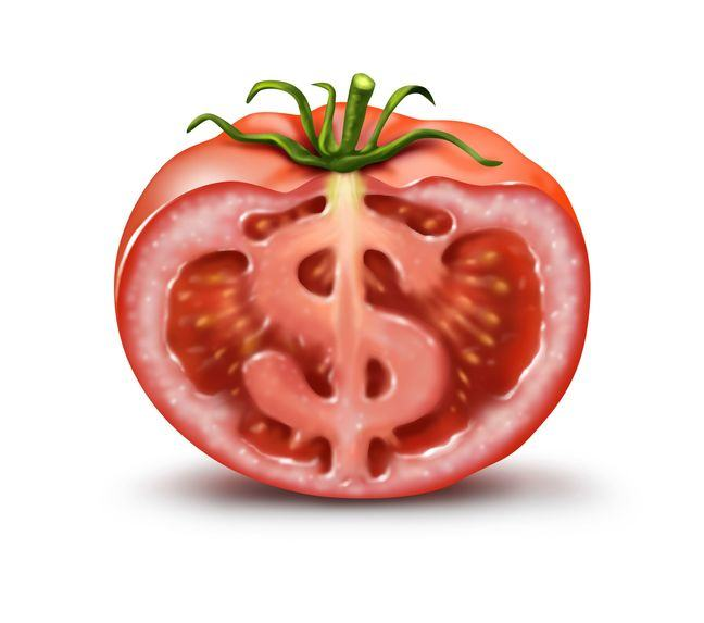A cartoon of a tomato cut in half, with an image of a dollar sign ($) making up the central core of the fruit