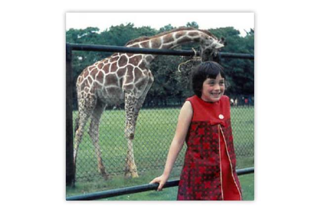 A photo of a girl in a red dress in front of a giraffe at the zoo