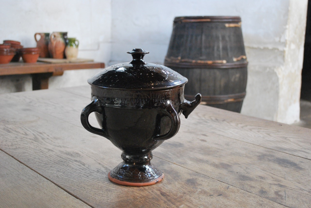 A black bowl that has a foot and a stem, with a black lid
