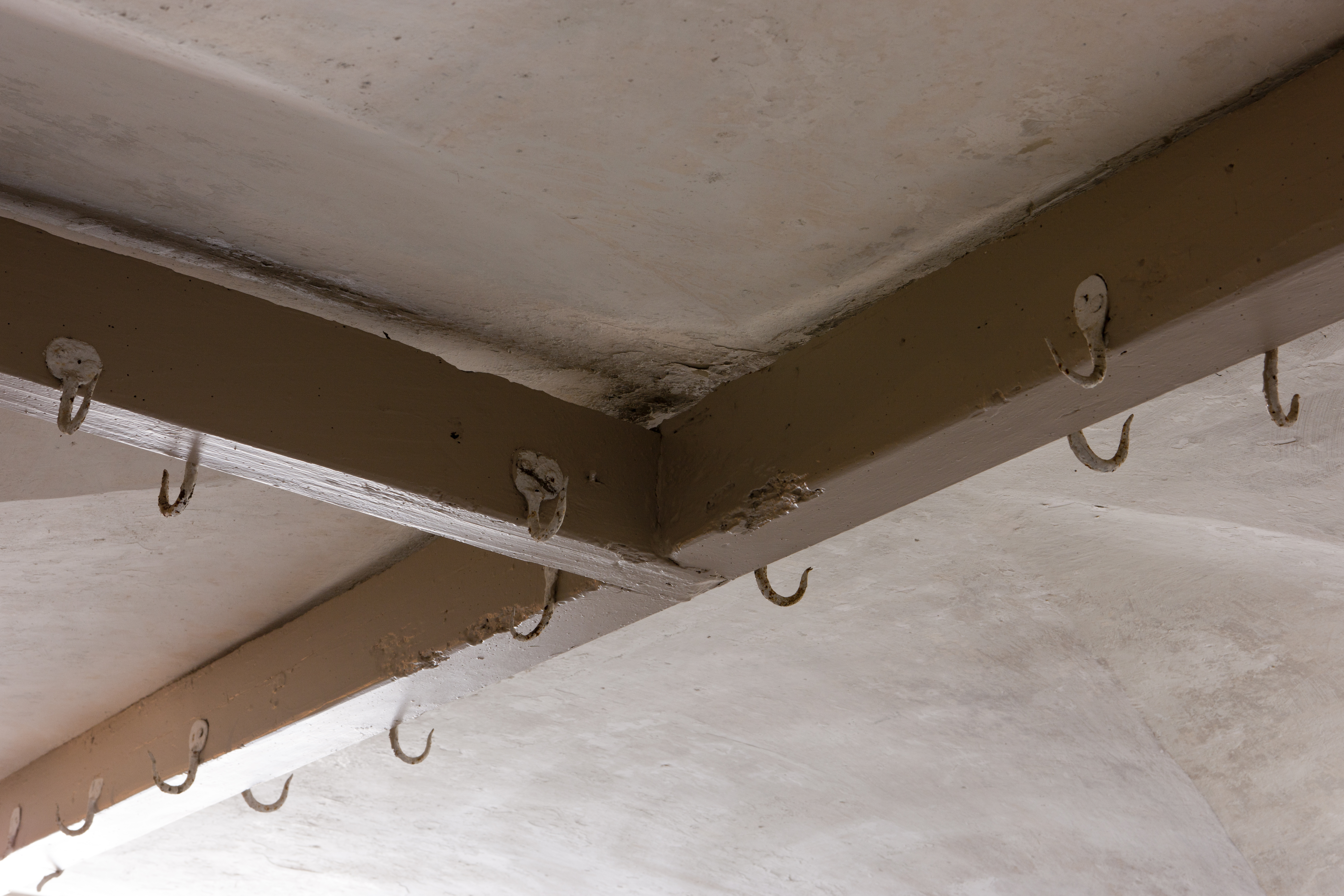 Hooks hanging off the ceiling of a kitchen