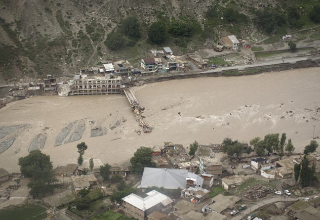 Photograph of Pakistani flood survivors lining up beside the damaged bridge and river in full spate in Medain, a town in the Swat Valley, northern Pakistan, on August 2, 2010