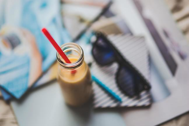 overhead view of a bottle of milky drink with a straw, sunglasses and notebook in the background