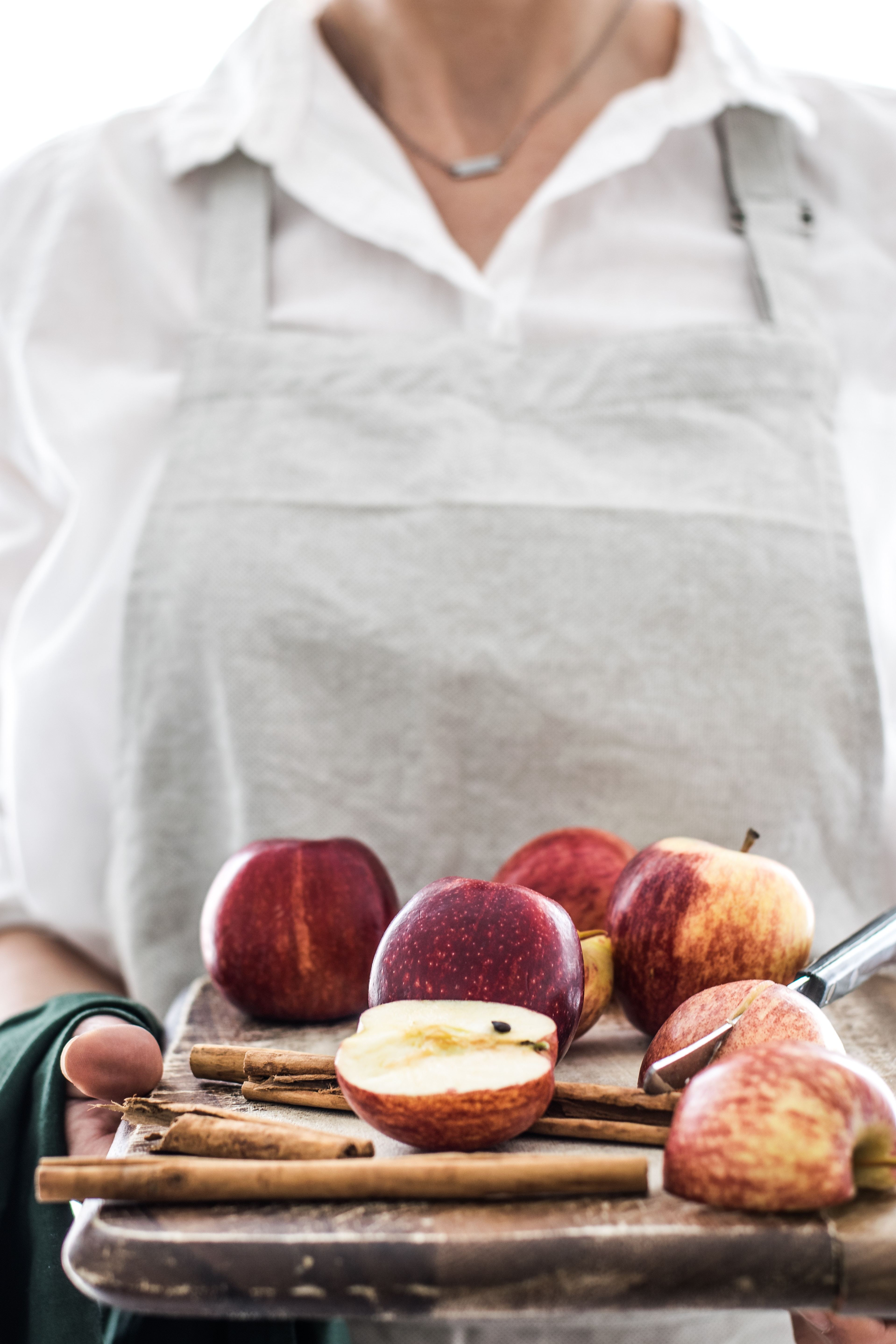 woman holding a board containing apples, some chopped in half
