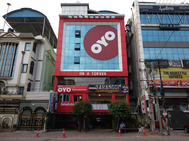 Facade of a hotel with a three story high Oyo logo extending across the front of the hotel.