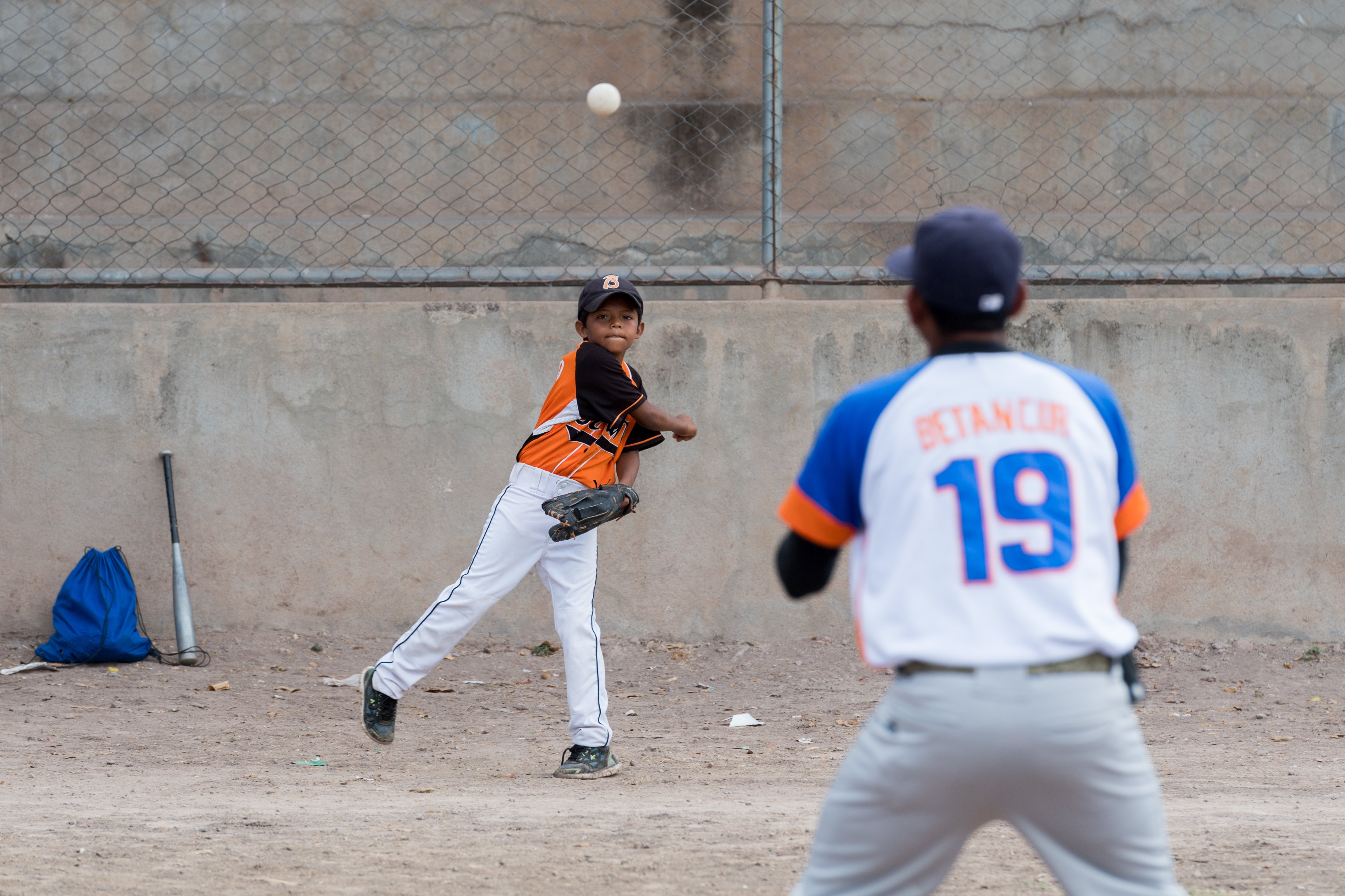 A boy in baseball gear is throwing a ball to his coach