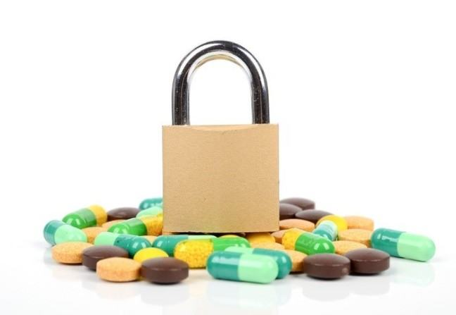picture of a padlock on top of a pile of pills
