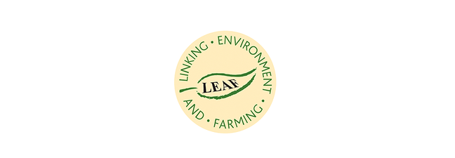 LEAF logo is a cream circle with a green leaf in the middle, and the words LEAF written in black in the middle of the leaf. Around the circle the words Linking Environment And Farming in green font