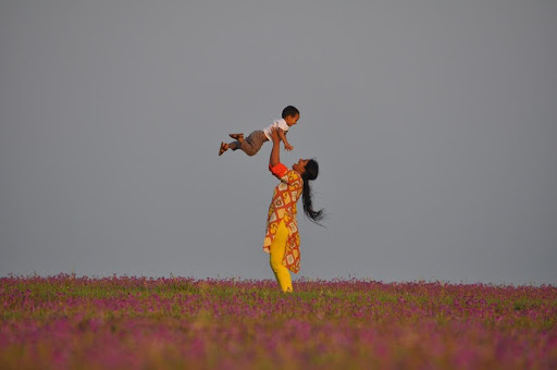 A colour photograph of a mother, wearing a yellow and orange shalwar kameez, lifting her child high above her head playfully