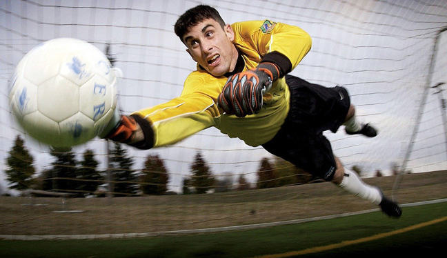 Football in air as goalkeeper attempts to save it