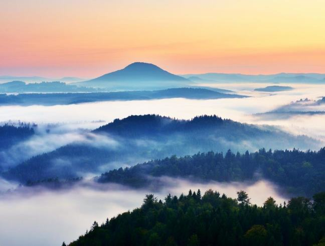 Photograph of fog sitting in valleys across a range of hills