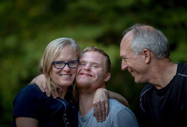 A young man with Down syndrome being hugged by his parents