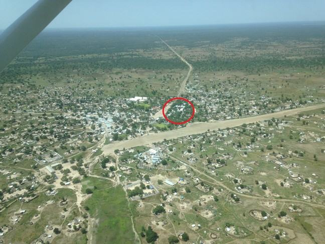 An aerial view of Lankien in South Sudan. There is a red circle showing where the hospital is. The landscape is mostly flat and green (but barren) with some buildings. There is an airport runway with an airplane on the tarmac. There is a forest in the distance.