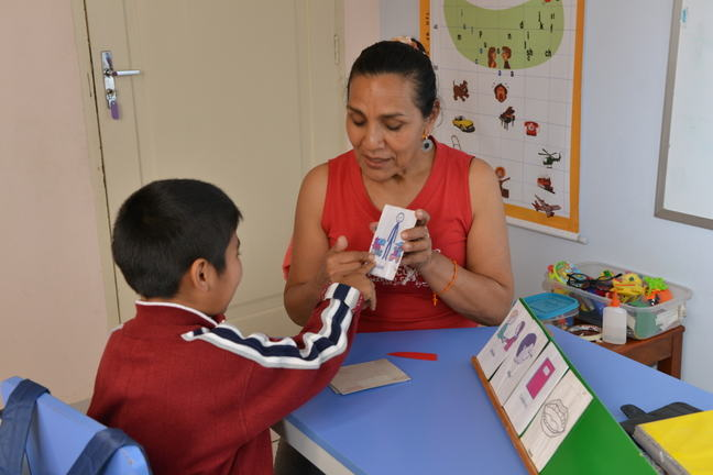 A boy is pointing at a picture card being held up by a woman.