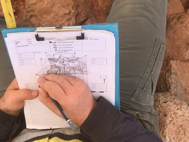 An archaeologist carefully recording a stratigraphic sequence on a clipboard