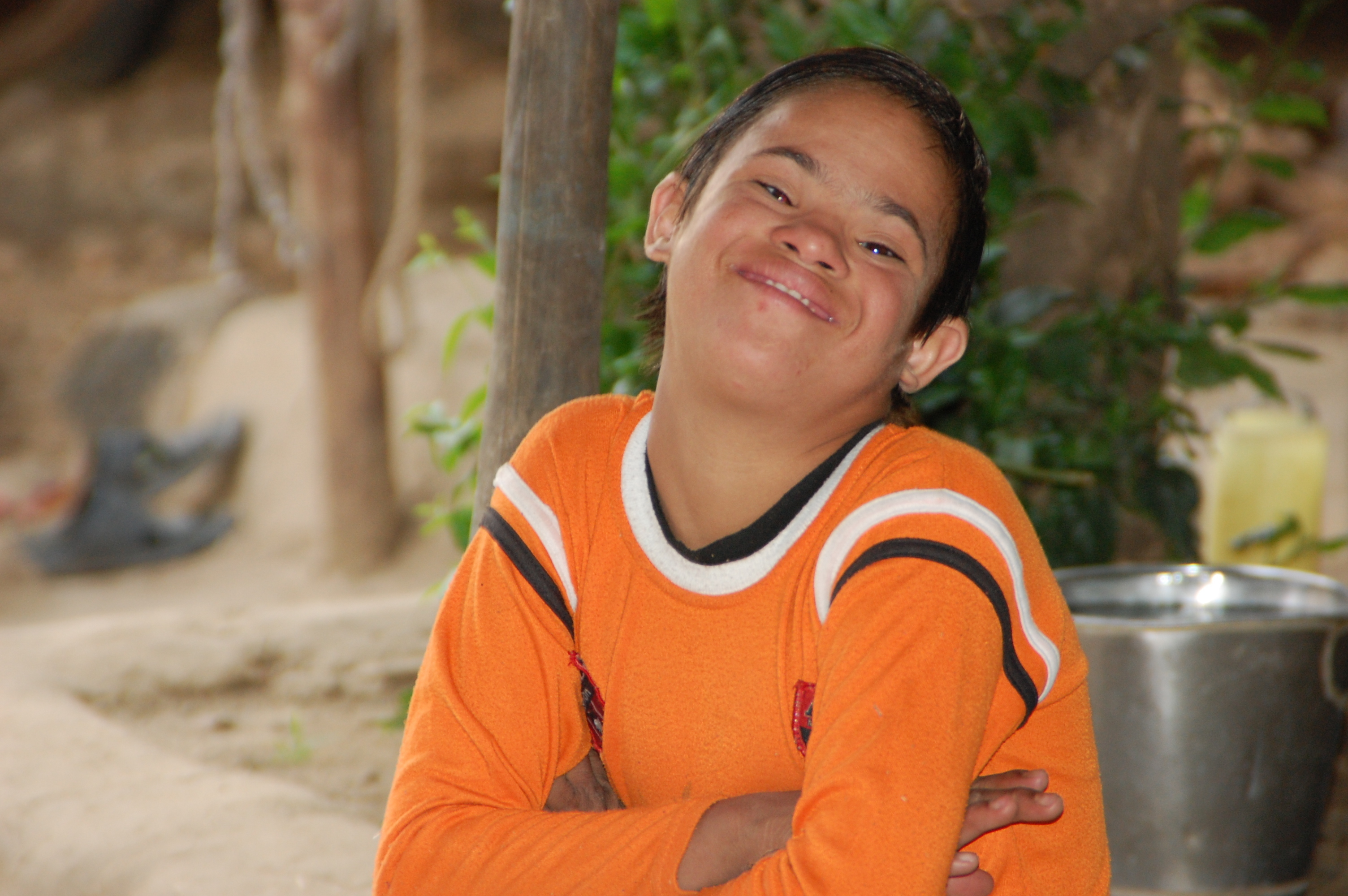 A boy with Down syndrome has his arms crossed and is smiling at the camera.