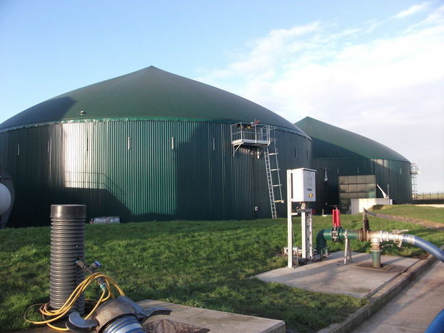 A photo of 2 large green digesters that are round both with a coned roof