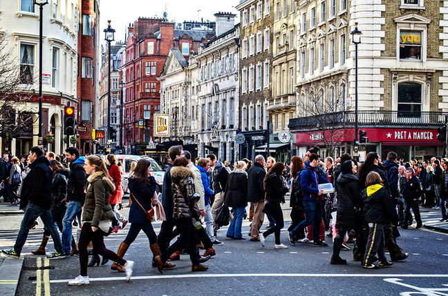 People crossing the street on a busy London road with coffee shops in the background