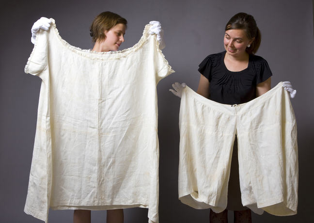 Two people holding up a chemise and drawers to show size
