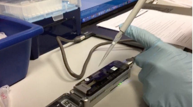 A black, portable device for DNA and RNA sequencing is at the top of a table. It is connected to a computer by a USB cable. A person with a gloved hand is holding a pipette with its end pointing towards the device.