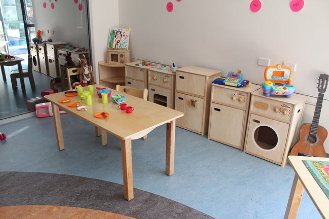 photograph of a table of play doh in an early childcare centre that has no chairs